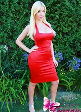 Sexy blonde tranny with a gigantic rack poses in a tight red dress